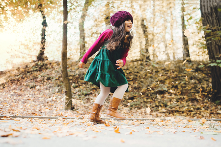 A portrait of a small toddler girl running in forest in autumn nature.