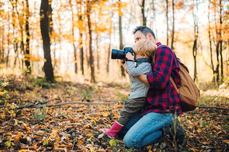 A mature father and a toddler son in an autumn forest, taking pictures with a camera. Foto de archivo - 111331090