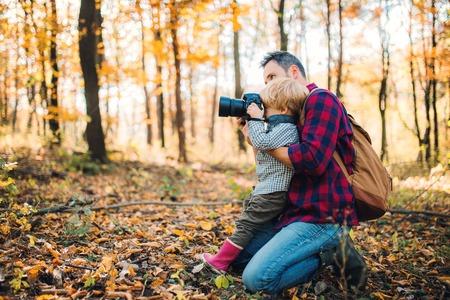 Un padre maturo e un figlio in una foresta autunnale, scattano foto con una macchina fotografica.