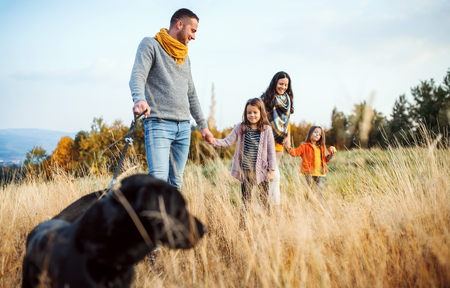 A young family with two small children and a dog on a walk in autumn nature. 版權商用圖片 - 111627156