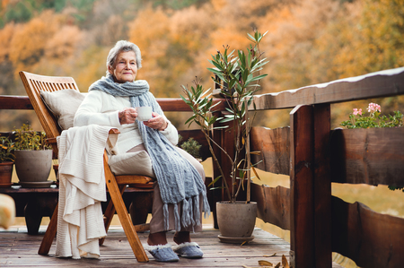 An elderly woman with a cup sitting outdoors on a terrace on a sunny day in autumn.