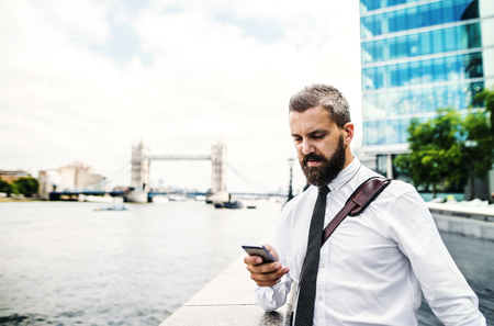 Hipster businessman with smartphone standing by the river in London, texting. Reklamní fotografie