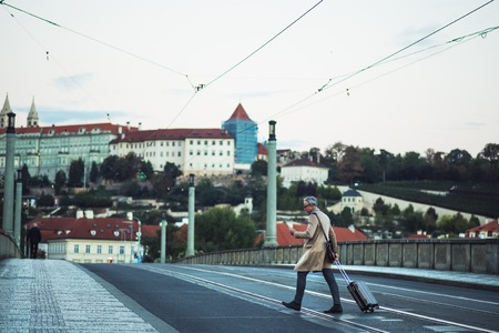A businessman with smartphone and suitcase crossing a road in Prague city. Stockfoto
