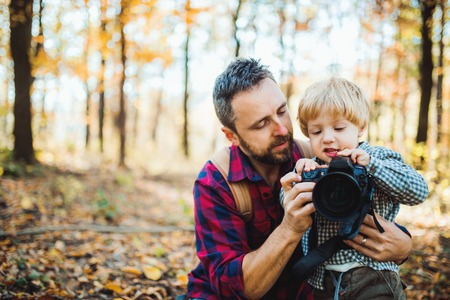 A mature father and a toddler son in an autumn forest, taking pictures with a camera. 版權商用圖片 - 111663720