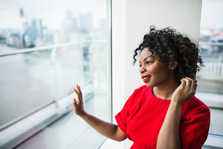 A portrait of woman standing by the window against London view panorama. Stock Photo