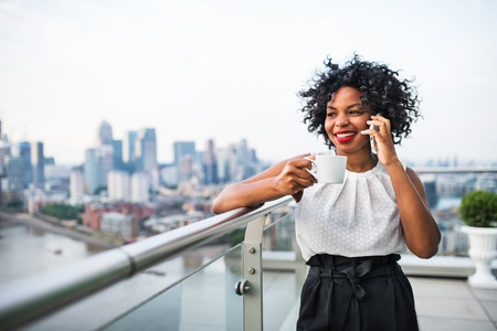 A businesswoman standing against London view panorama, making a phone call. Stock Photo