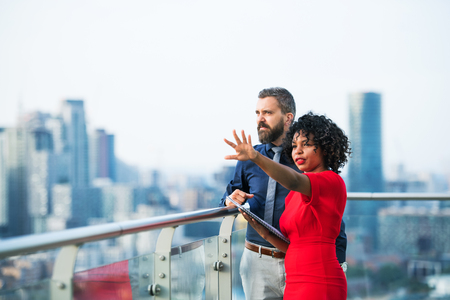 A portrait of two businesspeople standing against London view panorama, talking.