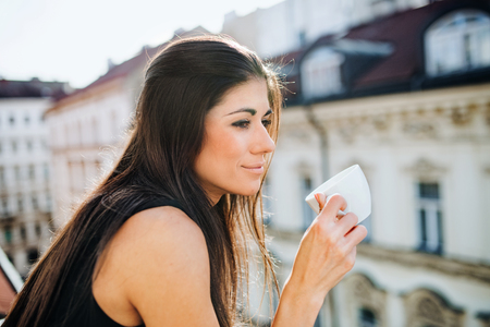 Young businesswoman with cup of coffee standing on a terrace in an office in city.