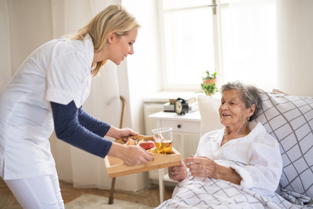 A health visitor bringing breakfast to a sick senior woman lying in bed at home. Stockfoto