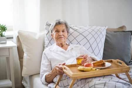 A sick senior woman with food on a wooden tray lying in bed at home.
