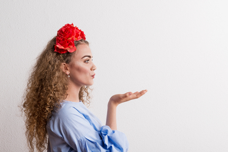 A side view of young beautiful woman with flower headband sending a kiss in studio. Фото со стока