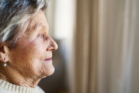 A close-up portrait of a senior woman at home, looking out of a window. Reklamní fotografie