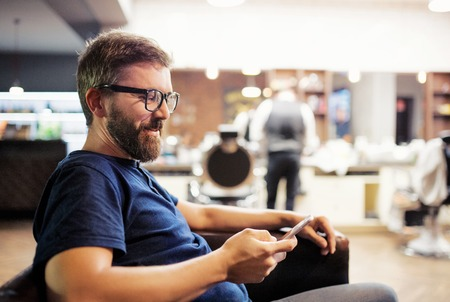 Hipster man client visiting haidresser and hairstylist in barber shop, waiting. Stock Photo