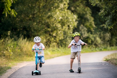Two small boys with a helmet riding scooters on a road in park on a summer day.