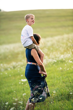 A young mother giving piggyback ride to small son in nature on a summer day. Stock Photo