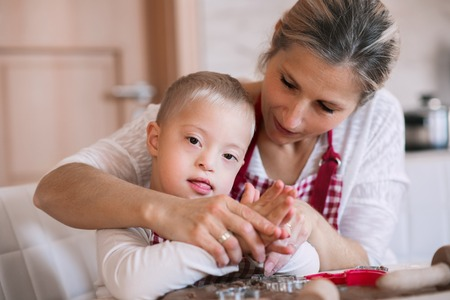 A handicapped down syndrome boy with his mother indoors baking. Stock Photo - 111779911