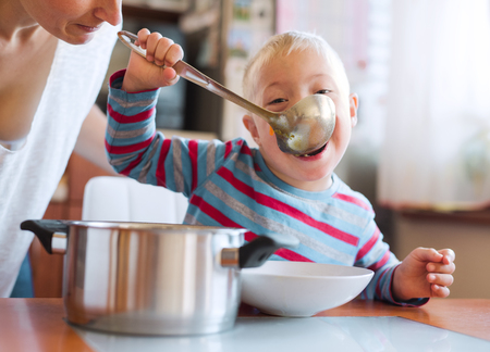 A handicapped down syndrome boy eating soup from a ladle indoors, lunch time. Foto de archivo - 111779920