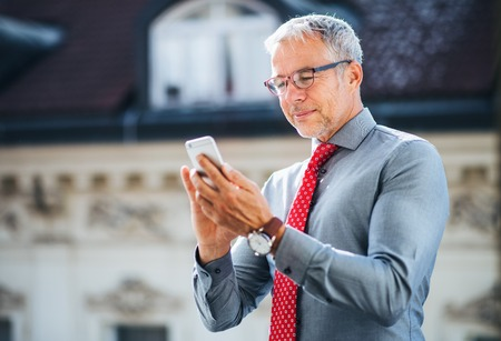 Mature businessman with smartphone standing on a terrace in city, texting. Stock fotó
