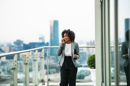 A portrait of a businesswoman standing on a terrace, making a phone call. Stock Photo