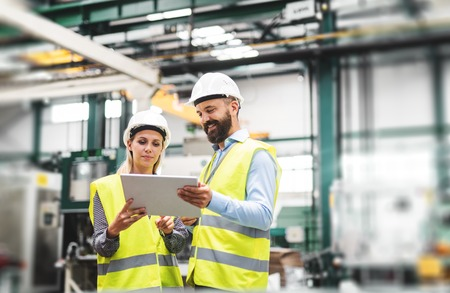 A portrait of an industrial man and woman engineer with tablet in a factory, talking. Banque d'images
