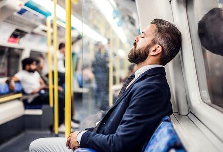 Schlafender Hipster-Geschäftsmann innerhalb der U-Bahn in der Stadt, die zur Arbeit reist. Standard-Bild