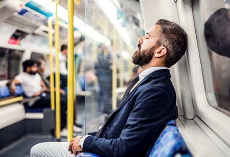 Uomo d'affari hipster addormentato all'interno della metropolitana in città, in viaggio per lavoro. Archivio Fotografico