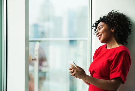 A portrait of woman standing by the window, holding smartphone.