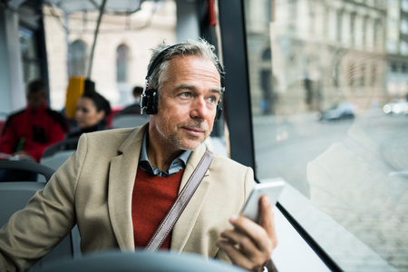 Mature tired businessman with heaphones and smartpone travelling by bus in city. Reklamní fotografie