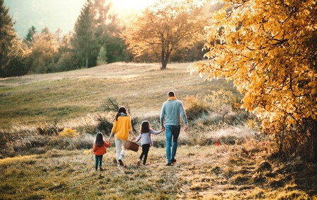 A rear view of young family with two small children walking in autumn nature. Standard-Bild - 112226341