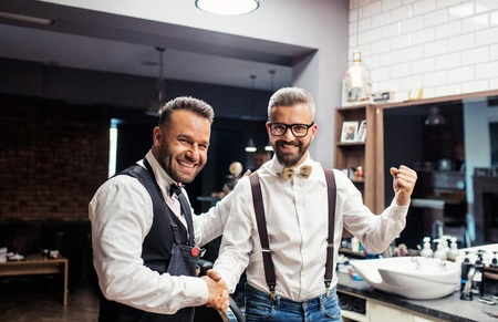 Hipster man client shaking hands with haidresser and hairstylist in barber shop.