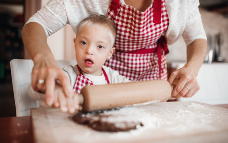 A handicapped down syndrome child with his mother indoors baking.