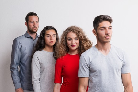 Portrait of young group of friends standing one after another in a studio.