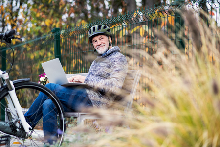 A senior man with electrobike sitting on a bench outdoors in town, using laptop.