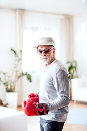 A senior man with boxing gloves having fun at home.
