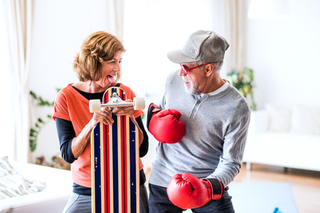 Senior couple with boxing gloves and longboard having fun at home.