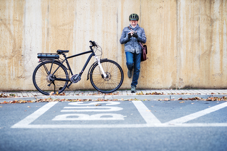 Active senior man with electrobike standing outdoors in town, using smartphone. Stock Photo - 112228295