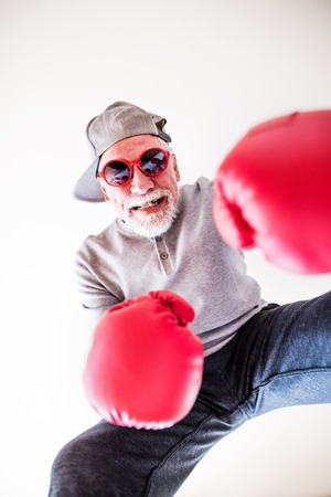 A senior man with sunglasses and boxing gloves having fun at home.