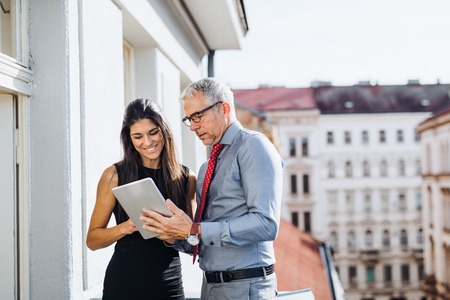 Man and woman business partners with tablet standing on a terrace in city, talking. Stok Fotoğraf