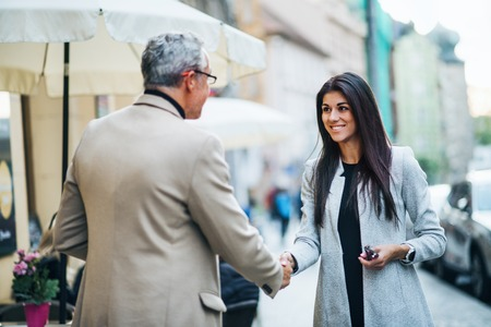 Man and woman business partners standing outdoors in city of Prague, shaking hands.
