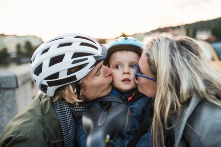 A small toddler boy with helmet and young parents outdoors in city, kissing.