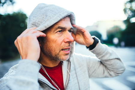 A portrait of an active mature man standing outdoors in city, putting on hood.