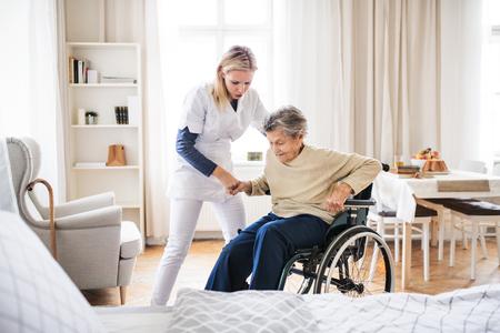 Ein Gesundheitsbesucher, der einer älteren Frau hilft, aus einem Rollstuhl aufzustehen.