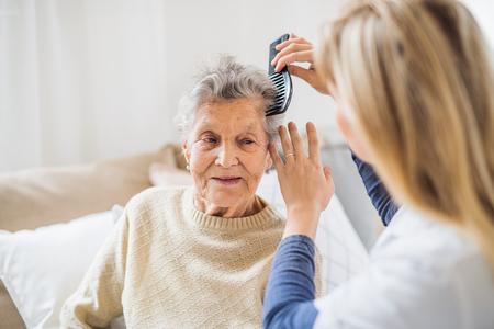 Een gezondheidsbezoeker die het haar van een oudere vrouw thuis kamt..