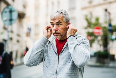 A portrait of an active mature man with earphones standing outdoors in city.