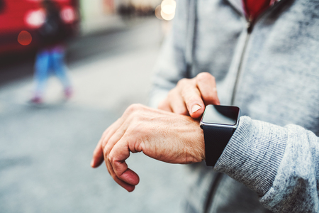 A close-up of unrecognizable man standing outdoors in city, using smartwatch. Stock Photo