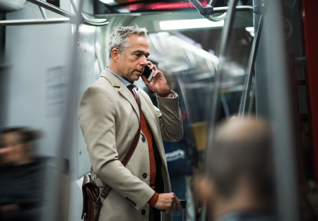 Mature businessman with smartphone travelling by subway in city. Archivio Fotografico - 112561464