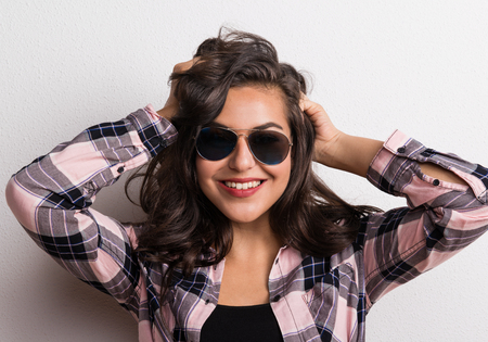 Young beautiful happy woman with sunglasses in studio.