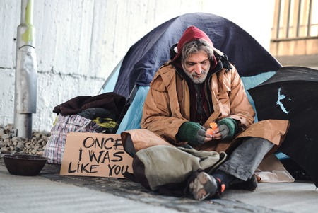 Homeless beggar man sitting outdoors in city asking for money donation. Standard-Bild