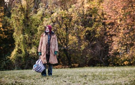 Homeless beggar man standing outdoors in park, holding bag. Copy space. Stock fotó