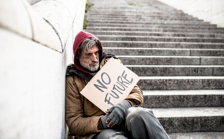 Homeless beggar man sitting outdoors in city holding no future cardboard sign.